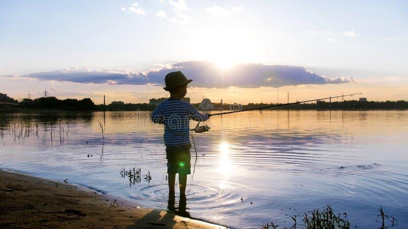 Un niño pequeño que pesca en la orilla del río en la puesta del sol fotografía de archivo