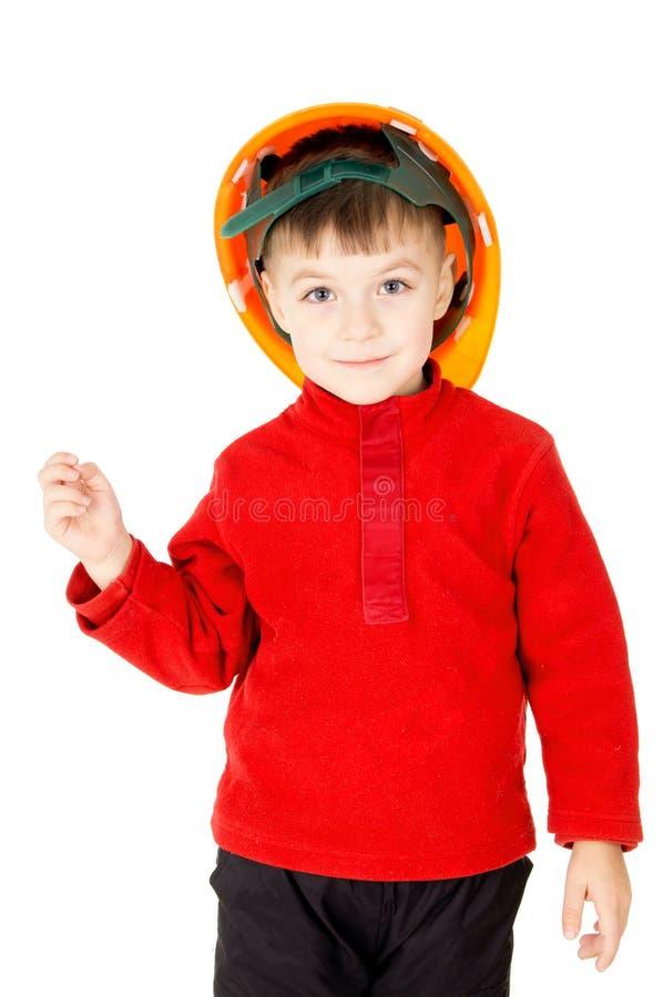 Un niño pequeño que se coloca con un casco foto de archivo libre de regalías