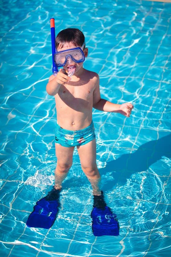 Un niño pequeño que se coloca en una piscina fotografía de archivo