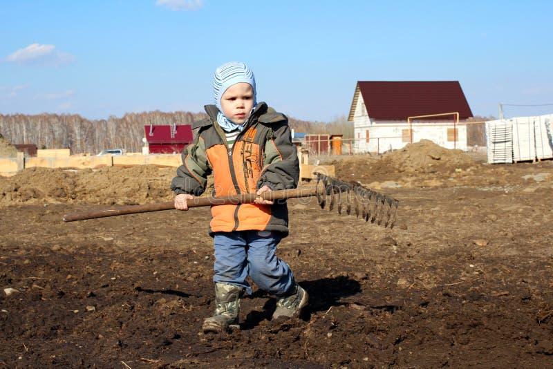 Un niño pequeño que sostiene un rastrillo grande en sus manos ayuda a trabajar en la tierra fotos de archivo libres de regalías