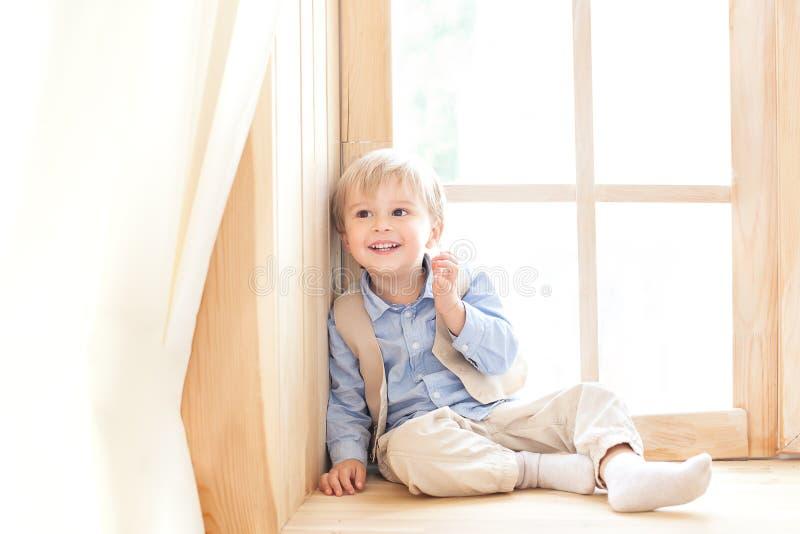 Un niño pequeño se está sentando en el alféizar en el cuarto de niños El concepto de ocio, de ocio, de gente y de forma de vida R foto de archivo