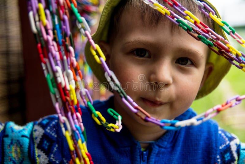 Un niño pequeño sonriente en un sombrero amarillo y un suéter azul está mirando a través de una cadena coloreada imagen de archivo