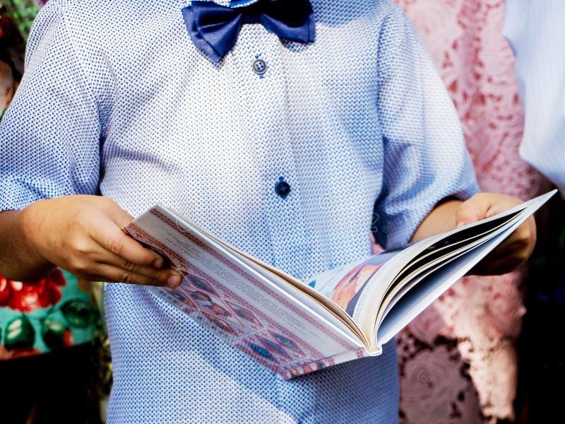Un niño pequeño sostiene en sus manos un libro revelado Lectura inter fotografía de archivo libre de regalías