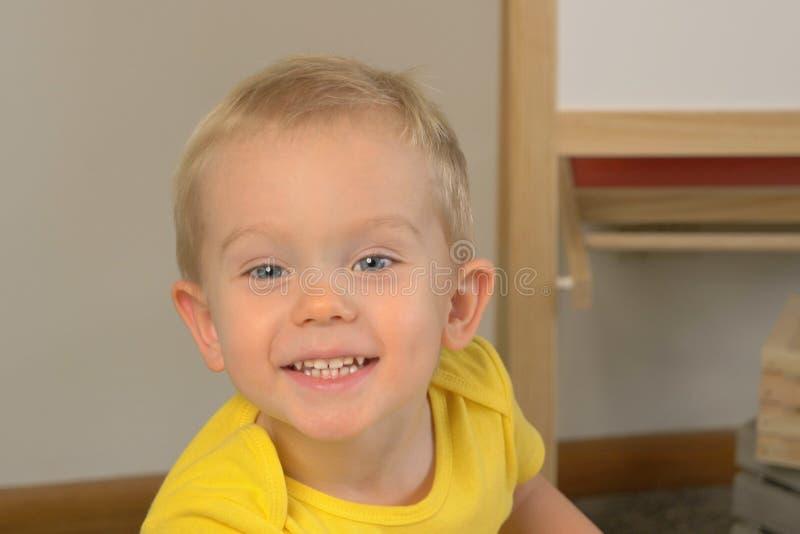 Un niño preescolar lindo de dos años que sonríe y que mira fotografía de archivo libre de regalías