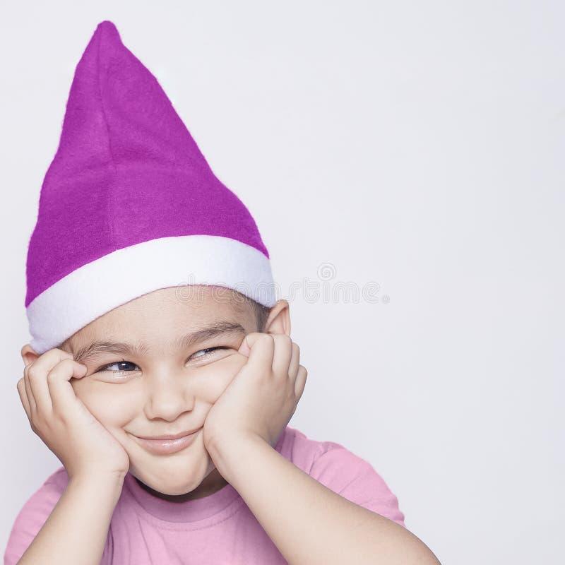 Un niño que hace la cara enfadada divertida Muchacho enfadado de la Navidad en Santa Hat imagen de archivo