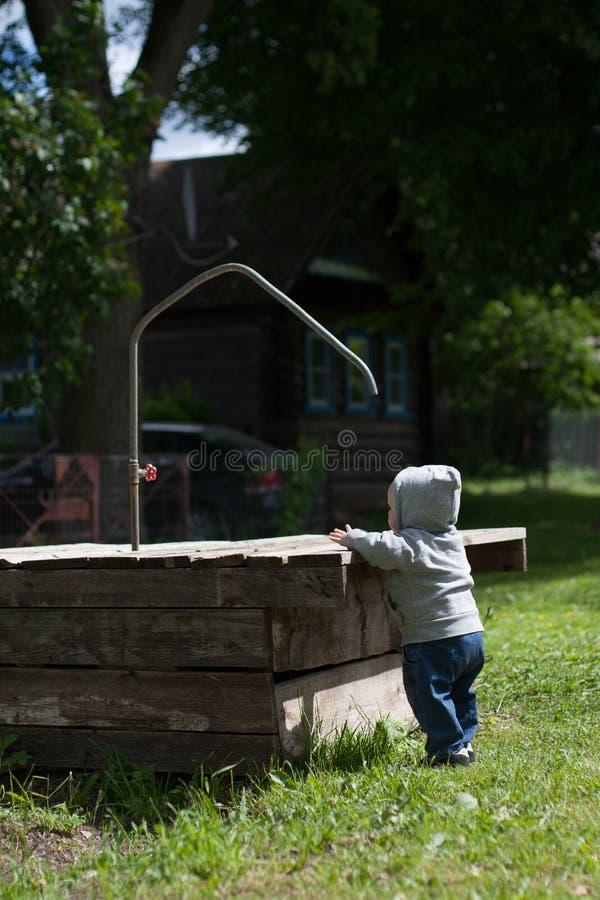 Un niño que juega al aire libre con un utensilio de riego fotografía de archivo