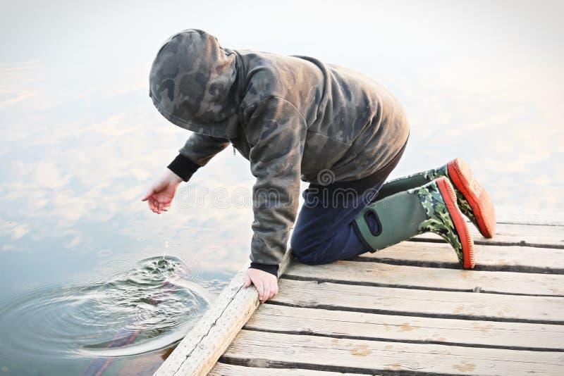 Un niño que juega con agua de un muelle imagenes de archivo