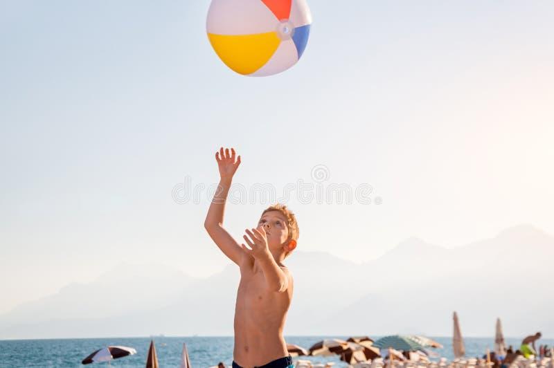 Un niño que juega con la pelota de playa imagen de archivo