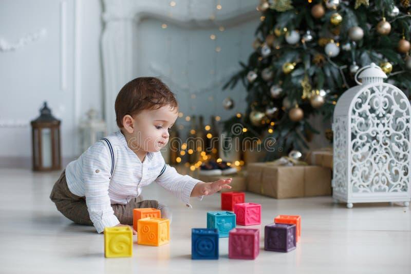 Un niño que se sienta en el piso cerca de un árbol de navidad elegante, jugando con los cubos coloreados fotos de archivo