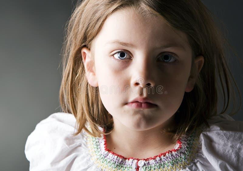 Un niño rubio joven mira la cámara en la preocupación fotos de archivo libres de regalías