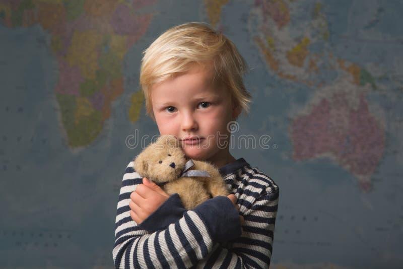 Un niño rubio lindo abraza su peluche delante de un mapa del mundo fotos de archivo