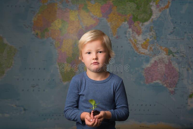 Un niño rubio lindo sostiene un almácigo delante de un mapa del mundo fotografía de archivo
