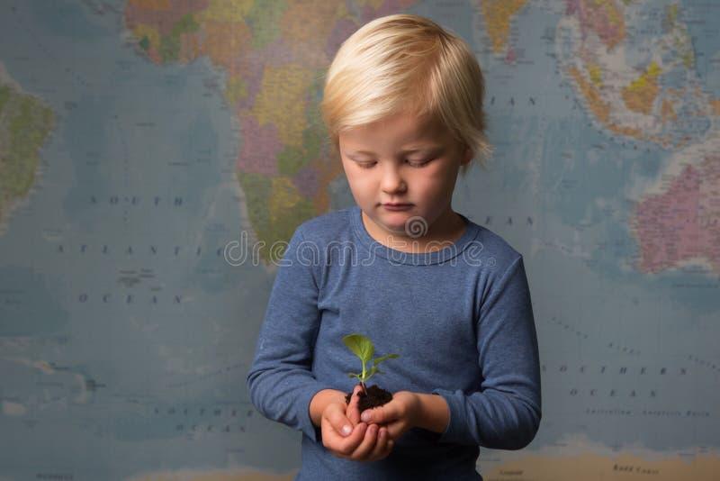 Un niño rubio lindo sostiene un almácigo delante de un mapa del mundo fotografía de archivo libre de regalías