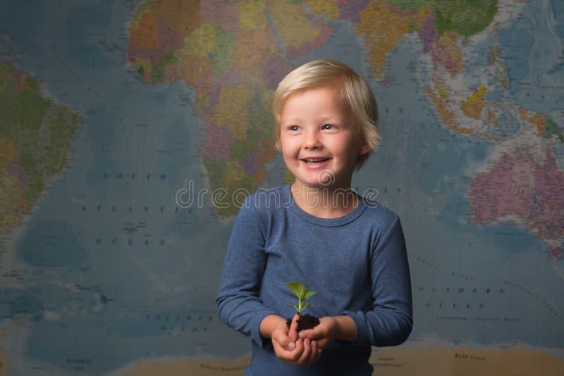 Un niño rubio lindo sostiene un almácigo delante de un mapa del mundo fotos de archivo