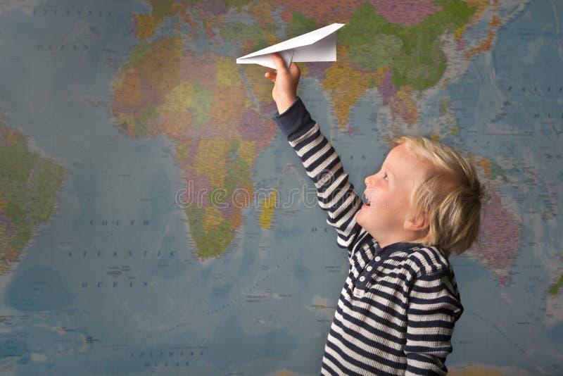 Un niño rubio lindo vuela un avión de papel delante de un mapa del mundo fotografía de archivo