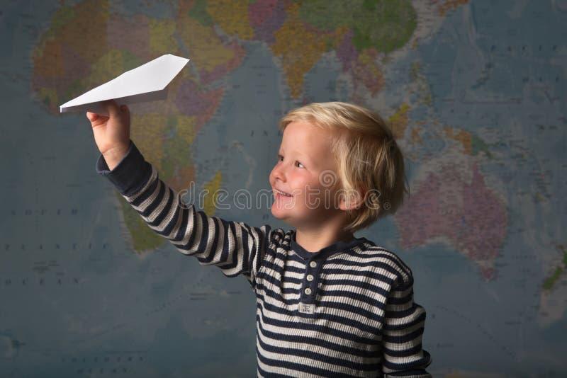 Un niño rubio lindo vuela un avión de papel delante de un mapa del mundo fotos de archivo
