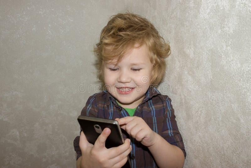 Un niño satisfecho es feliz que a le se permitió jugar con su smartphone de los parent's imagen de archivo