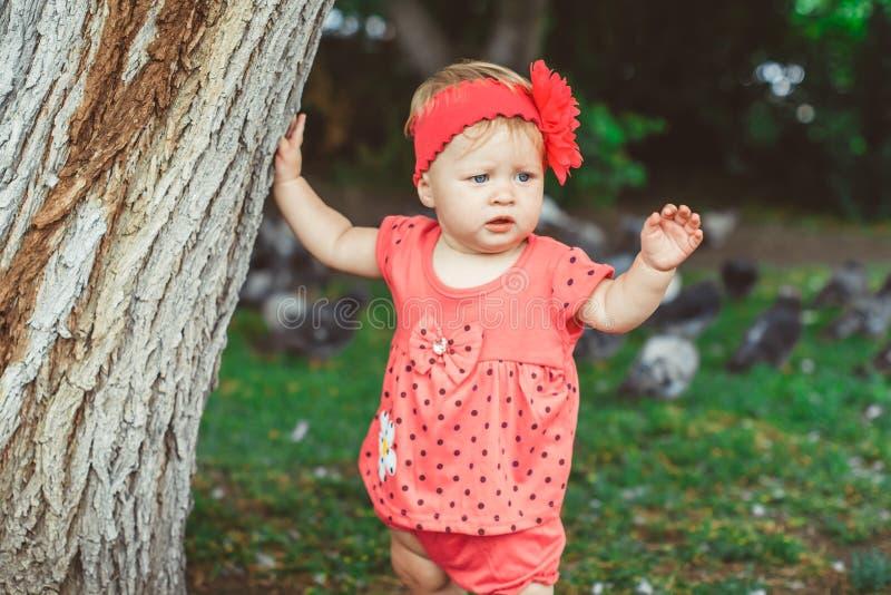 Un niño se coloca cerca de un árbol imagen de archivo