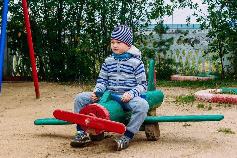 Un niño se sienta en un avión de madera en el patio fotos de archivo