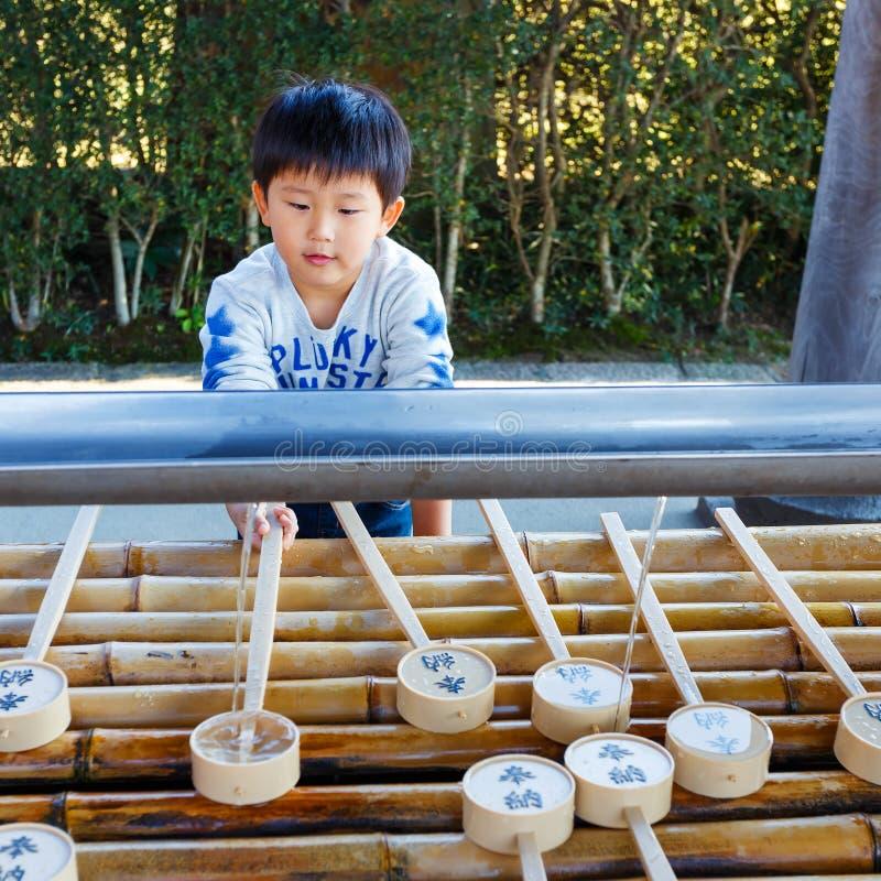 Un niño utiliza el cazo del agua en el templo de Todaiji en Nara imagen de archivo libre de regalías