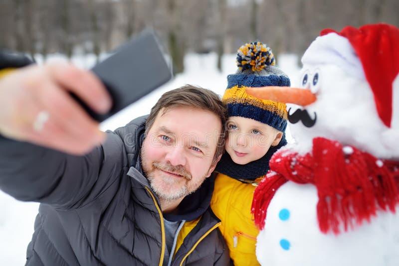 Un niño y su padre se toman selfie en el fondo de un muñeco de nieve en un parque de nieve. Actividad al aire libre con niños e fotografía de archivo