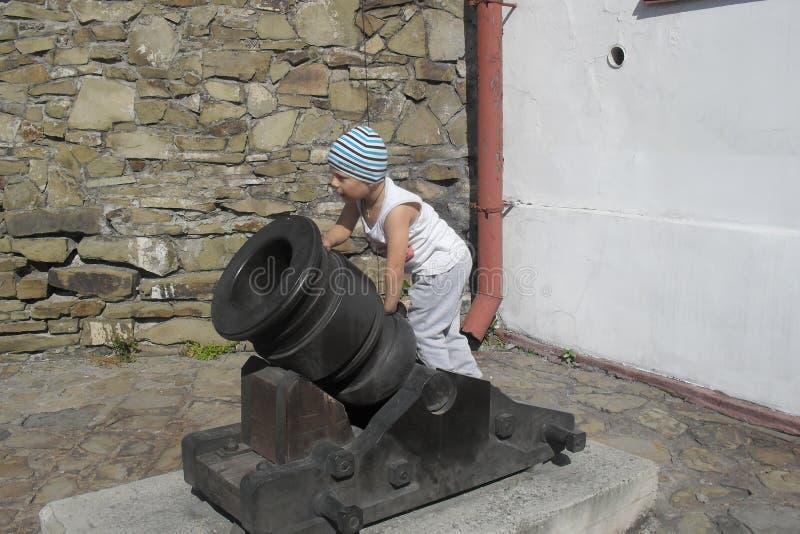Un niño y un cañón viejo imagen de archivo libre de regalías