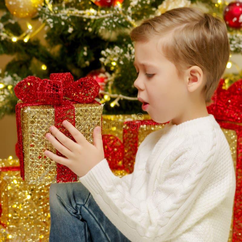 Un ni?o peque?o cerca del ?rbol de navidad con un regalo imagen de archivo libre de regalías
