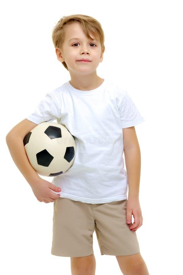 Un ni?o peque?o que lleva una camiseta blanca pura est? jugando con un socc imagen de archivo
