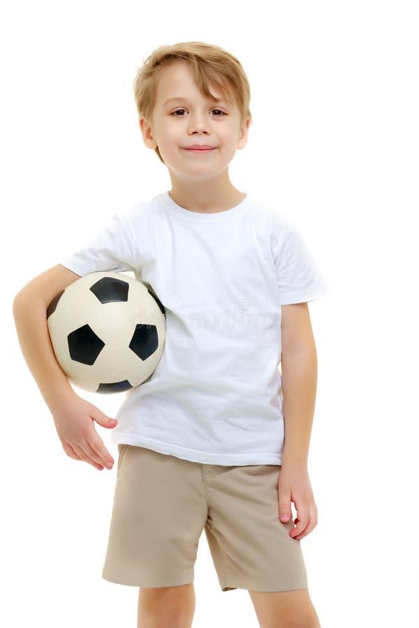 Un ni?o peque?o que lleva una camiseta blanca pura est? jugando con un socc imagen de archivo libre de regalías
