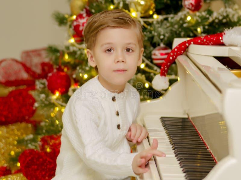Un ni?o peque?o se est? sentando en el piano cerca del ?rbol de navidad imagen de archivo libre de regalías