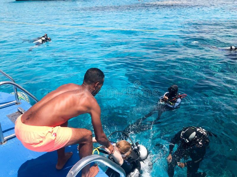 Un noir, plongeurs de aide d'homme sportif sportif basané et arabe dans les costumes noirs de plongée à l'air avec des bouteilles photo libre de droits
