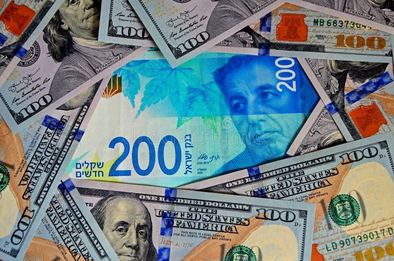 Un nouveau billet de banque de 200 shekels israéliens et de beaucoup de factures de 100$ Vue supérieure, fond photographie stock