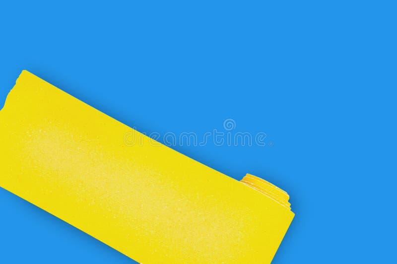 Un nouveau rouleau de papier sablé abrasif jaune pour des articles en bois ou en métal de grille sur la table bleue dans l'atelie illustration de vecteur
