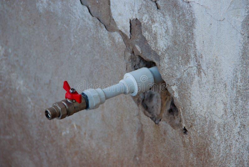 Un nouveau tuyau en plastique avec le robinet rouge sortant du vieux mur photos stock