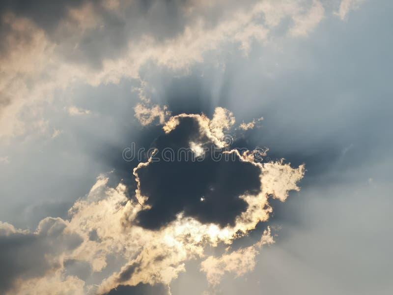 Un nuage noir avec le soleil dans le ciel bleu photos libres de droits