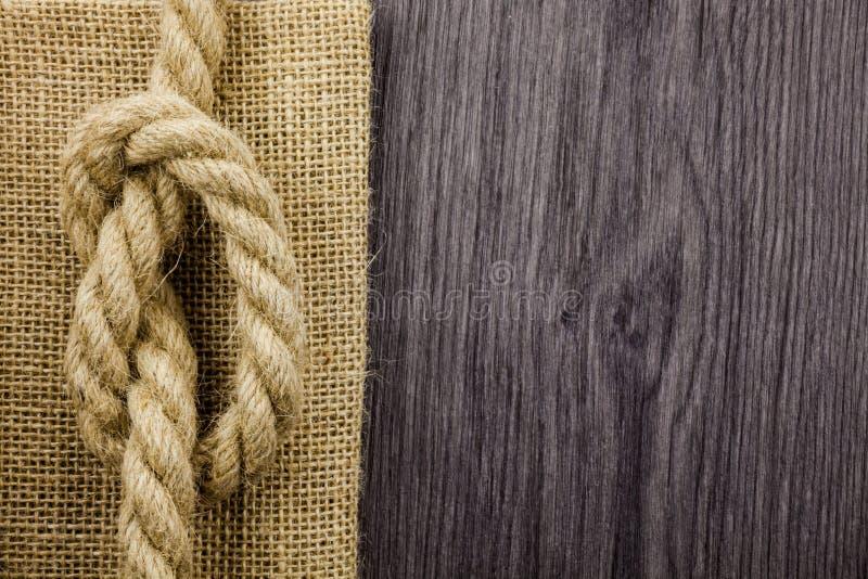 Un nudo en una cuerda en un tablero de madera con el espacio de la copia Huevas viejas con el nudo imágenes de archivo libres de regalías