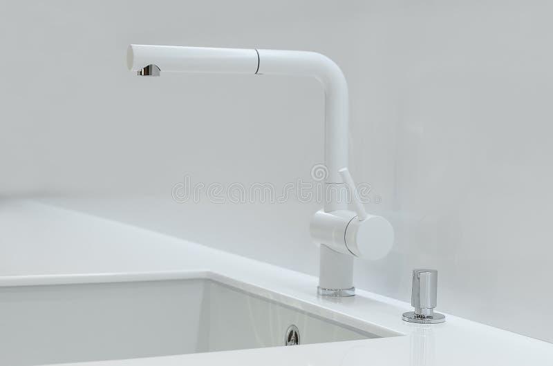 Un nuevo fregadero de cocina blanco hecho de piedra artificial y de un grifo El concepto de interior moderno de la cocina foto de archivo libre de regalías