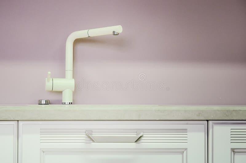 Un nuevo fregadero de cocina blanco hecho de piedra artificial y de un grifo El concepto de interior moderno de la cocina fotos de archivo