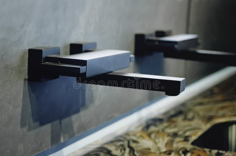 Un nuevo fregadero de cocina negro hecho de piedra artificial y de un grifo El concepto de interior moderno de la cocina imagenes de archivo