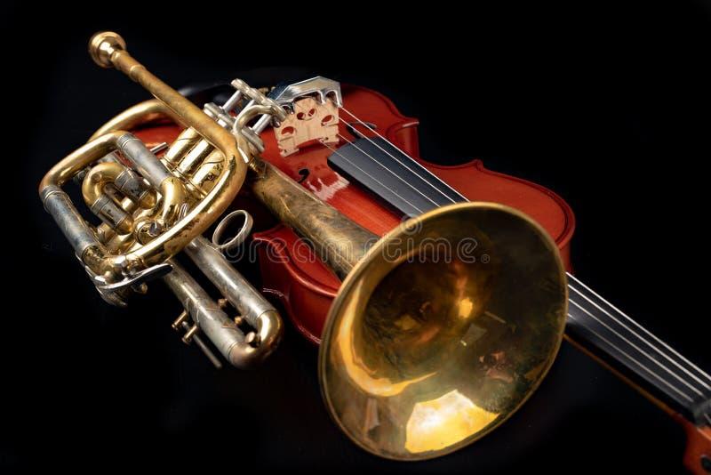 Un nuevo viol?n brillante y una trompeta vieja en una tabla oscura Instrumentos musicales, atados y viento fotos de archivo