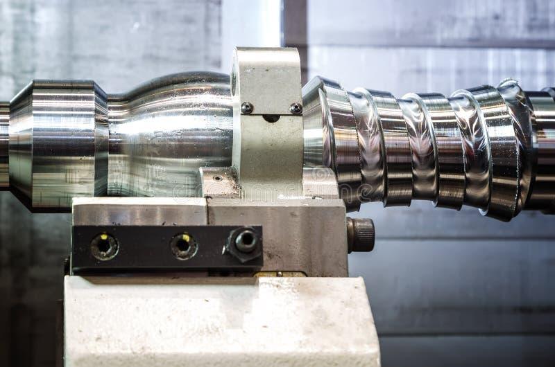 Un objeto del metal afianzado con abrazadera en la máquina del CNC de la tirada del torno Profundidad del campo baja foto de archivo libre de regalías