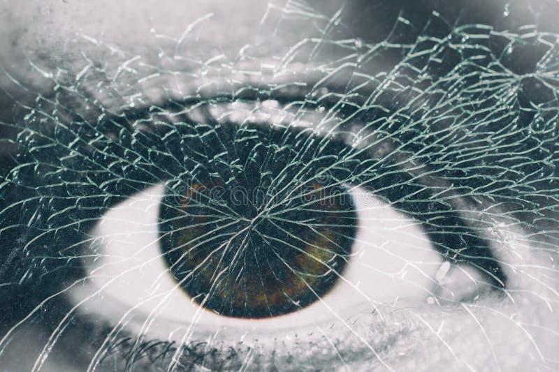Un occhio femminile dietro il vetro rotto fotografie stock libere da diritti