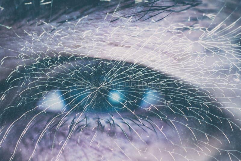 Un oeil masculin derrière le verre cassé image libre de droits