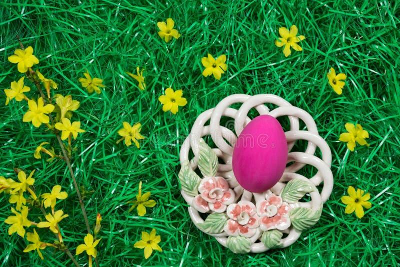 Un oeuf de pâques rose en cuvette décorative et fleurs jaunes dans l'herbe artificielle verte photo libre de droits