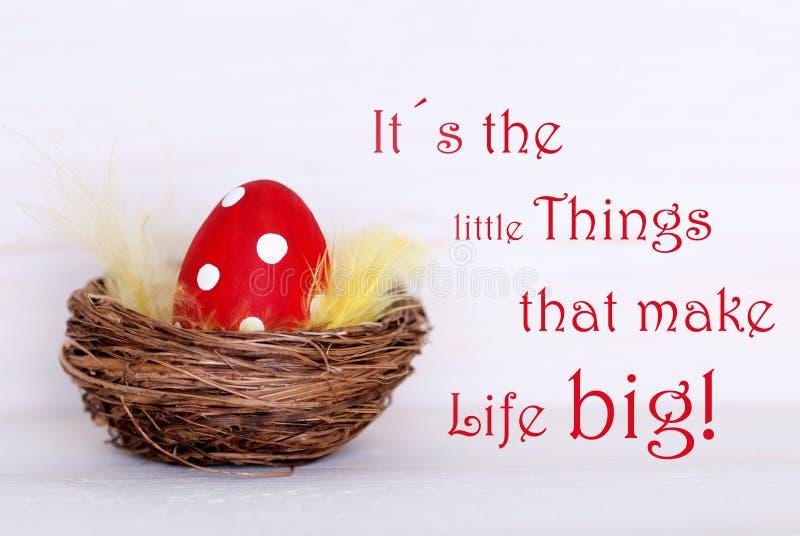 Un oeuf de pâques rouge dans le nid avec choses de citation de la vie de petites rendent la vie grande images stock