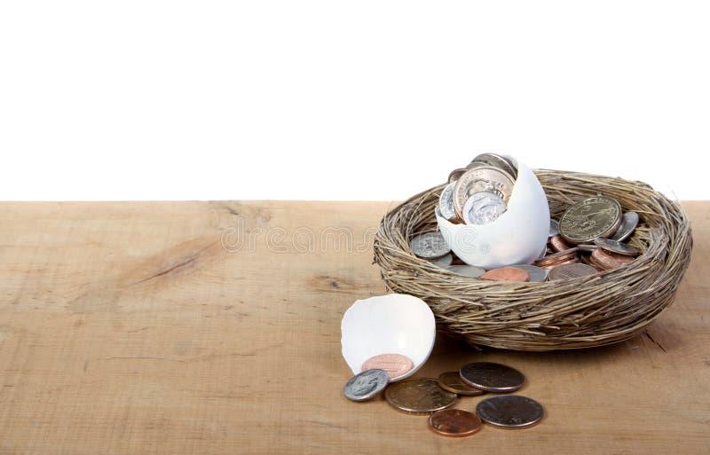Un oeuf ouvert criqué avec des pièces de monnaie se renversant à l'extérieur images libres de droits