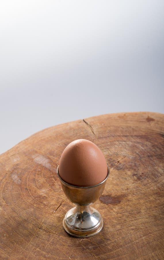 Un oeuf simple sur un oeuf de port de tasse au-dessus d'un bloc de bois photographie stock libre de droits