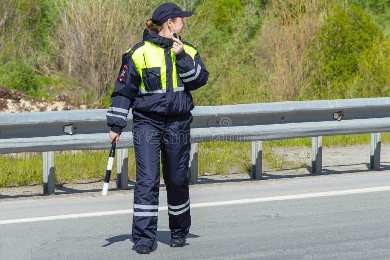 Un oficial de policía de la mujer está en el camino Visi?n trasera fotografía de archivo