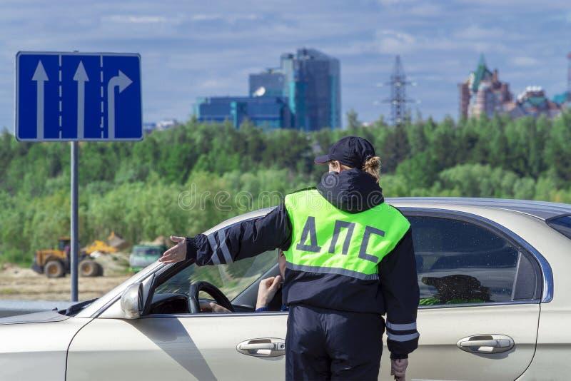 Un oficial de policía de la mujer que habla con el conductor del coche Visi?n trasera fotos de archivo