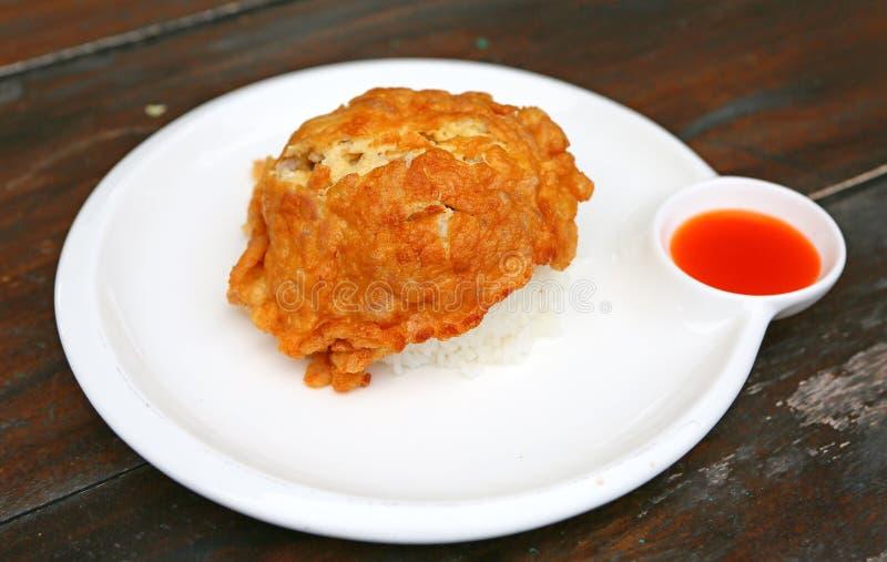 Un'omelette è un piatto fatto dalle uova battute cucinate rapidamente con burro o olio in una padella servito con riso ed i peper immagine stock libera da diritti